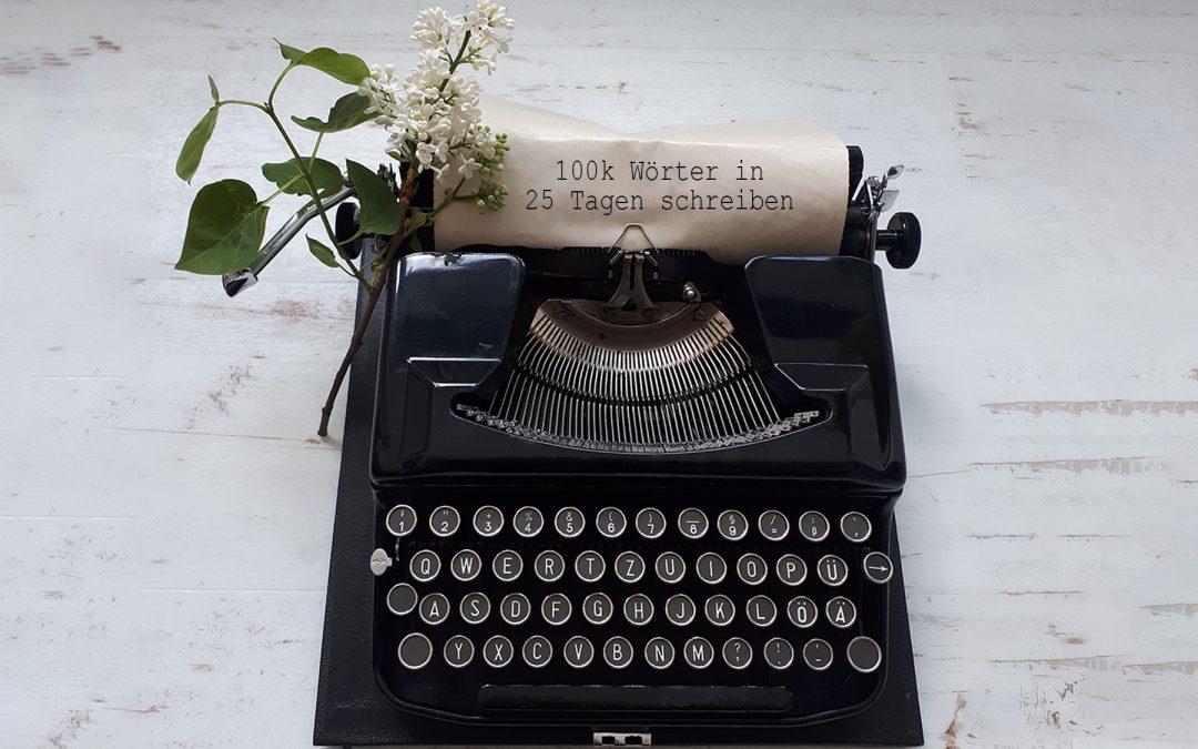 Schreibmaschine mit Papier auf dem steht: 100k Wörter in 25 Tagen schreiben